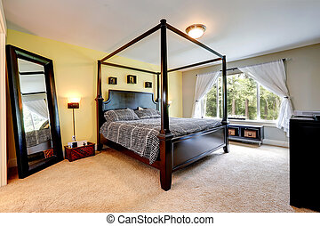 Carved wood bed with high poles. Bedroom interior