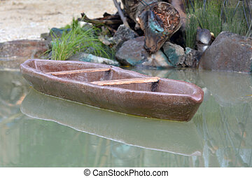 Carved wooden canoe on a body of water - A carved wooden...