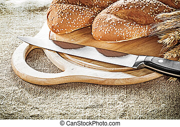 Carving board bread knife wheat ears on sacking background