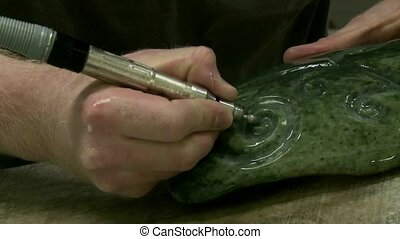 Carving Greenstone. - Hands of a carver working greenstone...