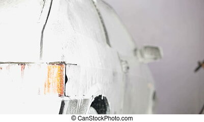carwash foam - worker puts on a car wash foam