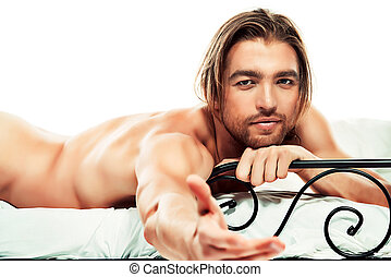 casanova man - Handsome nude man lying in a bed. Isolated...