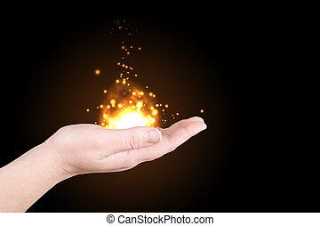 Cascade of sparks on a palm on a black background