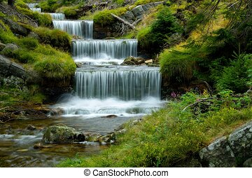 Amazing cascade in a wooded mountainous landscape