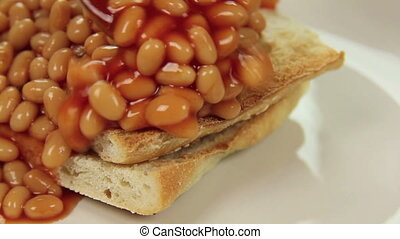 Close up of hot baked beans poured and cascading over crisp toast.