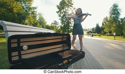 Case for violin lying on the bench in front of female who plays a fiddle at sunset