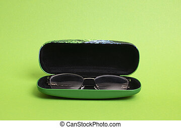 Case with glasses on a green background