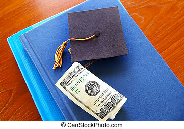 cash and small graduation cap on a pile of books