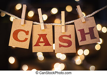 The word CASH printed on clothespin clipped cards in front of defocused glowing lights.