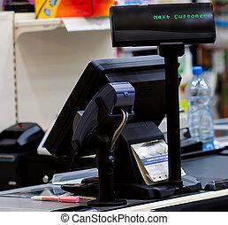 Cash desk with terminal in supermarket