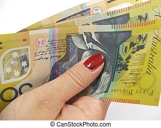 Woman holds Australian $50 notes in her hand