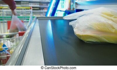 cash in the supermarket, a woman buys groceries at the...