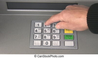 Cash machine withdrawal - A hand entering PIN code and...