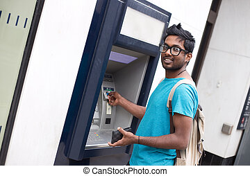 cash machine - young indian man at the cashpoint withdrwing...