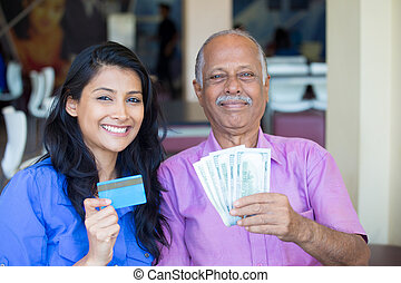 Closeup portrait rich elderly gentleman in pink shirt and lady in blue top holding greenbacks and credit card. Booming economy concept, buy, sell, award. Make money at home