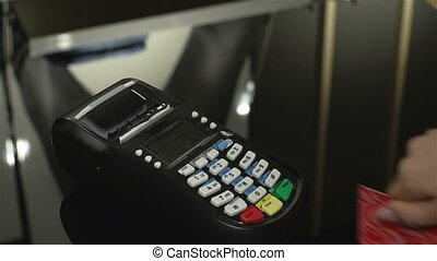 Cash Register - Close-up of a salesperson using a cash...