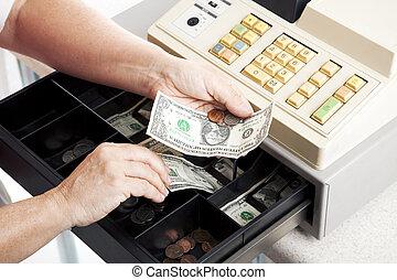 Horizontal view of an open cash register drawer asa a cashier makes change.
