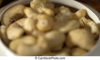 Cashew in white bowl. Dynamic change of focus