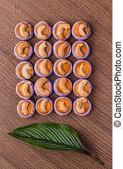 Cashew nut cookies and dry leaf on wooden background. Top view.
