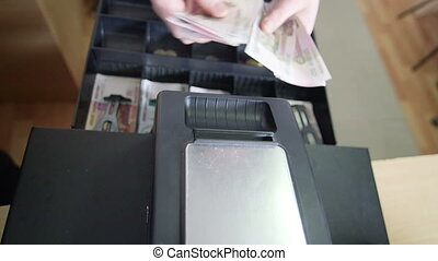 Cashier counts money from the till