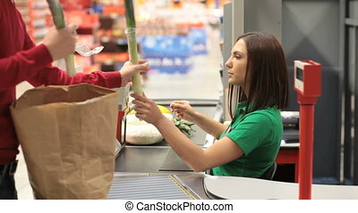 Friendly cashier behind checkout counter passing products to buyer