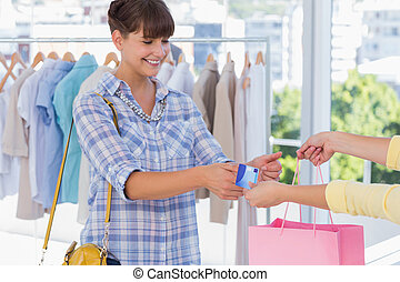 Cashier giving credit card to a smi