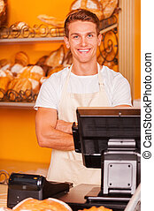 Cashier in bakery shop. Handsome young male cashier in apron keeping arms crossed and smiling while standing at the cash register in bakery shop