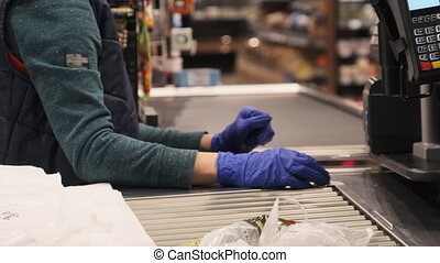 Cashier in gloves with the terminal at the checkout supermarket caters to the buyer. Payment through the terminal in the store. The seller at the cash register sells products. Close-up. Covid-19. 4K.