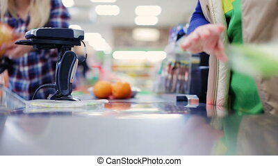 Cashier scans purchase products at point of sale - Cash desk...