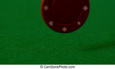 Casino chip falling on green table in slow motion