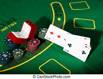 casino chips and a precious ring on green poker table background, man throws cards with losing combination.