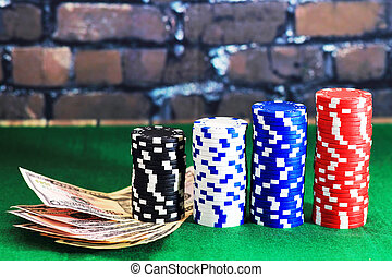 Casino chips and money on green poker table