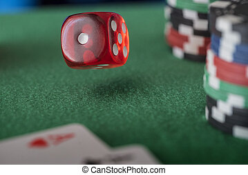 Casino chips, cards and red dices on green felt game table