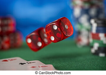 Casino chips, cards and two red dices on green felt game table