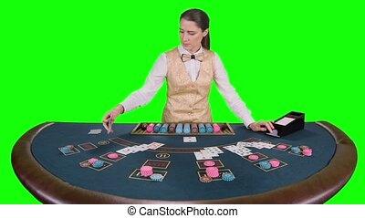 Casino croupier distributes for table poker three cards are the flop. Green screen. Slow motion