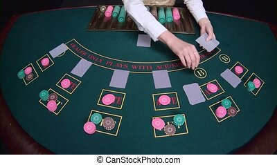 Casino croupier distributes for table poker three cards are the flop. Slow motion. Close up
