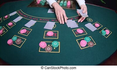Casino croupier distributes the cards. Slow motion. Close up