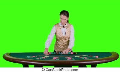 Casino croupier in a white shirt distributes for table poker three cards are the flop. Green screen. Slow motion