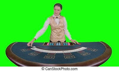 Casino croupier smoothes and gathers the poker cards. Green...