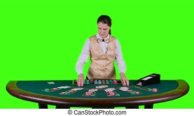 Casino croupier standing behind the semicircular desk in a white shirt distributes for table poker three cards are the flop. Green screen. Slow motion