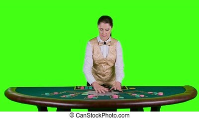 Casino female croupier standing at the table distributes the cards in the form of a arc on the poker table top. Green screen. Slow motion