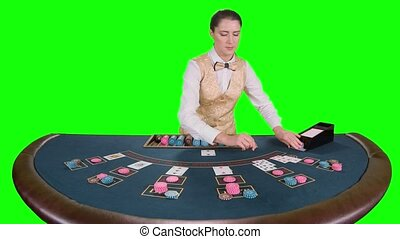 Casino female croupier standing at the table takes the cards...
