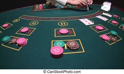 Casino female croupier takes the cards from card holder for game in poker. Slow motion. Close up