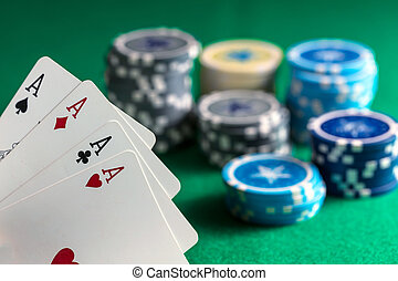Four aces and poker chips on green felt background
