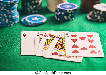 Casino, gambling concept. Hearts royal flush cards and poker chips on green felt