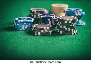 Poker chips piles on green felt background, copy space