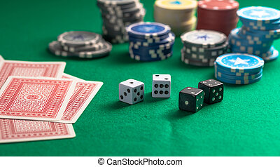 Casino, gambling. Poker chips piles, playing cards and dice on green felt background
