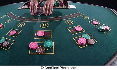 Casino hands croupier mixing cards on the table poker game. Slow motion. Close up