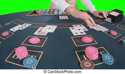 Casino hands croupier shuffle cards on the table poker game. Green screen. Slow motion. Close up