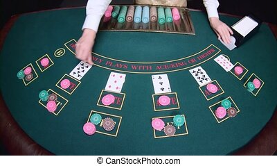 Casino hands croupier shuffle cards on the table poker game. Slow motion. Close up
